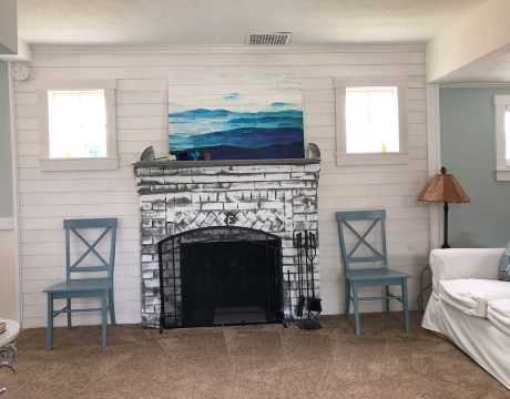 fireplace with two blue chairs