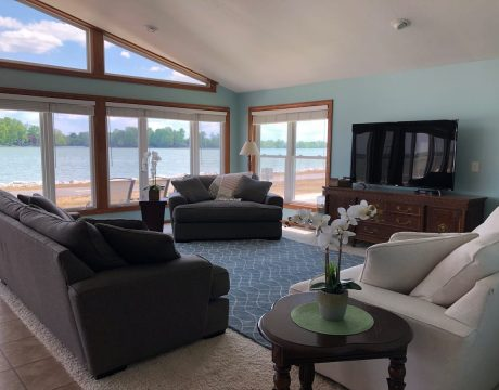 lakeside living room with couches, rug, tv, table