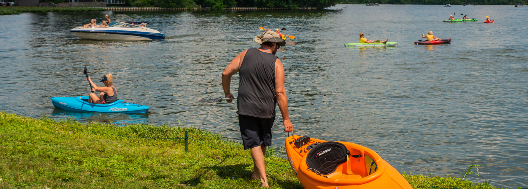 man on the grass with kayak heading to the lake