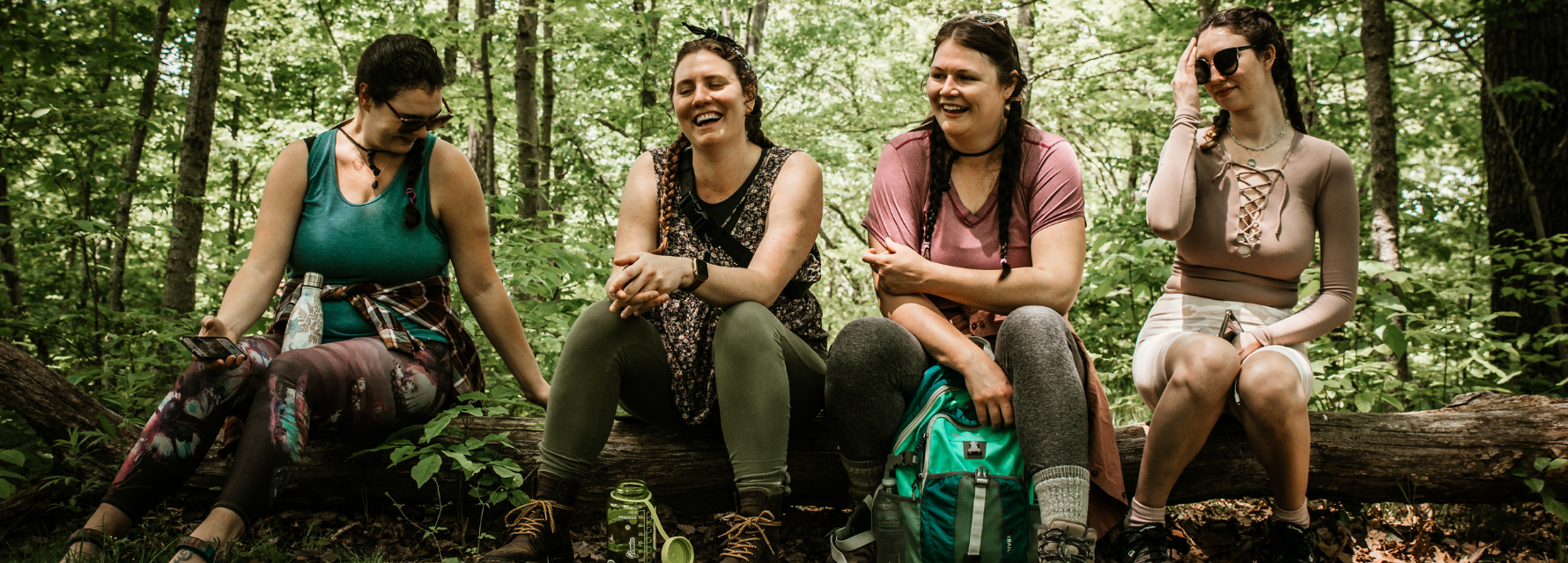 4 girls sitting on a log in the woods