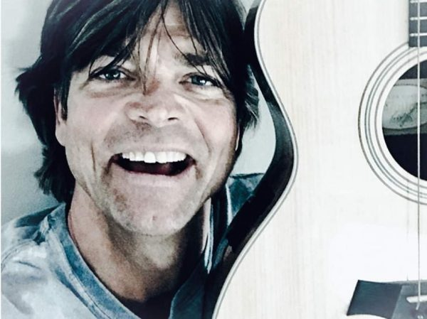 Man smiling with a guitar.