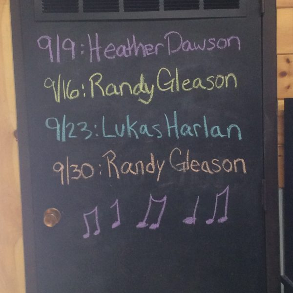 Chalkboard sign with names and dates of performances.