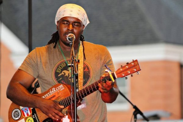 A man holding his guitar and singing.